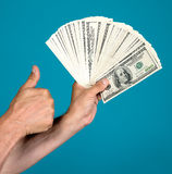 Man holding dollar bills and gesturing thumb up Royalty Free Stock Images