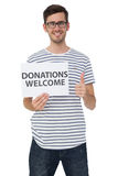 Man holding a donation welcome note while gesturing thumbs up Stock Image