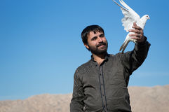 A Man Holding a Dove With Pride. A portrait of an Iraqi pigeon collector looking happy and holding a dove with pride front of him stock photo