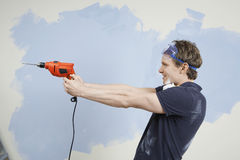 Man Holding Drill As Gun Against Wall Royalty Free Stock Photos