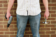 Man holding a drill and hammer Stock Image