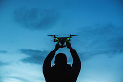 Man holding a drone for aerial photography. Silhouette against t Royalty Free Stock Photography