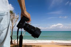 Man holding dslr digital camera on blurred beach and blue cloudy sky background. Photography hobby concept Royalty Free Stock Photography