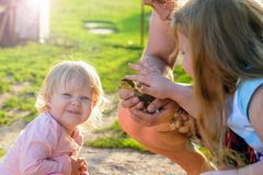 A man holding a duck chick. Men`s hands carefully hold the duckling showing it to little girls royalty free stock photo
