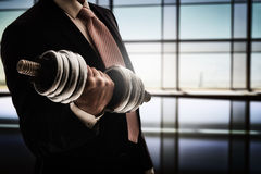 Man holding a dumbbell. Successful business man holding a heavy dumbbell. the concept of success in a hard work of business Stock Image