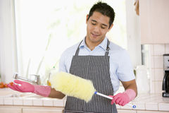 Man Holding Duster And Wearing Rubber Gloves Royalty Free Stock Photography