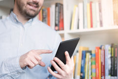 Man holding an e-book reader in hands Stock Photography