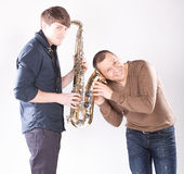 Man holding ear close to saxophone Royalty Free Stock Images