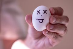 A man holding an egg with a funny face. Conceptual image stock image