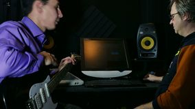 Man holding electric guitar in the recording studio sound mixing discussion stock footage