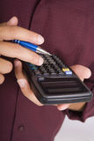 Man holding an electronic calculator Stock Image