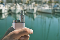 Man holding an electronic cigarette. Against the boats Royalty Free Stock Photos