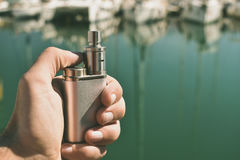 Man holding an electronic cigarette. Against the boats Royalty Free Stock Image