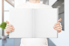 Man holding empty book. Casual young man holding empty open book in blurry interior. Mock up Stock Images