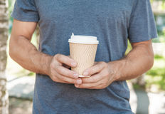 Man holding empty paper coffee cup. Template mock up Stock Images