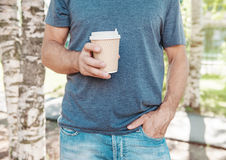 Man holding empty paper coffee cup. Template mock up Royalty Free Stock Photography