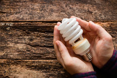 Man holding energy saving light bulb Royalty Free Stock Photos