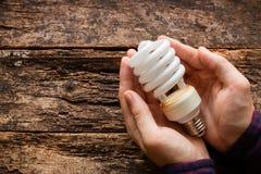 Man holding energy saving light bulb Royalty Free Stock Photos