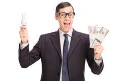 Man holding an energy saving light bulb and money Royalty Free Stock Photography