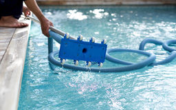 Man holding an equipment for cleaning  swimming pool. Man holding an equipment for cleaning the ground of the swimming pool Royalty Free Stock Image