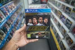 Man holding F1 2017 videogame on Sony Playstation 4 console in store. Bratislava, Slovakia, october 2 2017: Man holding F1 2017 videogame on Sony Playstation 4 Royalty Free Stock Images