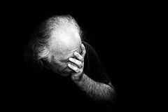 Man holding face in dispair. Gritty black and white image of older man holding head in despair, grain added to make more dramatic Stock Images