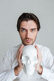 Man holding fake skull at his face Stock Photography