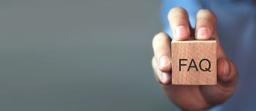 Man holding FAQ message on wooden cube. Frequently Asked Questions royalty free stock images