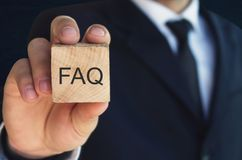 Man holding FAQ message on wooden cube. Frequently Asked Questions stock image