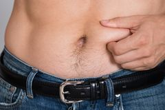 Man holding fat belly Stock Photo