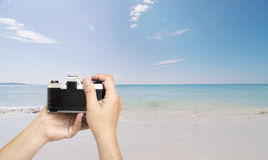 Man holding film camera ready to take photo over sea beach Stock Photo