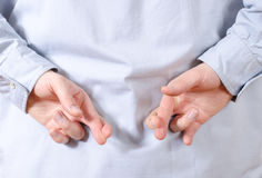 Man holding Fingers crossed behind his back Royalty Free Stock Images