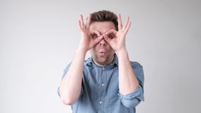 Man holding fingers near eyes like glasses. Mask like super hero or owl.