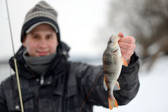 A man holding a fish caught. In the winter Royalty Free Stock Photos