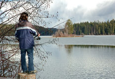 Man holding fishing rod. At a lake, with nice scenery Royalty Free Stock Photos