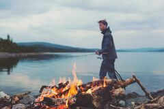 Man Holding Fishing Rod on Lake by Campfire Royalty Free Stock Photo