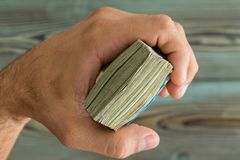 Man holding a fistful of banknotes over wood Stock Photo