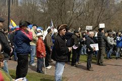 Man Holding Flag. Boston, Massachusetts USA - April 2013 - Man wearing brown Tricorn hat holding small flag while listening to speakers at the Boston Tea Party Royalty Free Stock Images