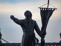 Man Holding a Flag. Statue of a man holding a flag, showing power with his hand Stock Image