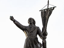 Man Holding a Flag. Statue of a man holding a flag, showing power with his hand Royalty Free Stock Photos