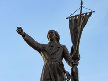 Man Holding a Flag. Statue of a man holding a flag, showing power with his hand Royalty Free Stock Image
