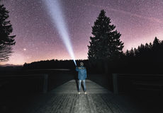 Man Holding Flashlight Standing in Wooden Surface Star Gazing Stock Photo