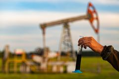 A man holding a flask of oil. Oil rigs in the background. Oil production in Russia. Sunset. Oil pumping stock images