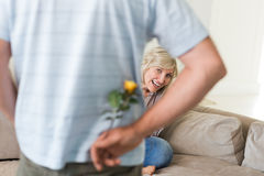 Man holding flower behind back with woman sitting on couch Royalty Free Stock Photography