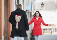 Man holding a flower bouquet behind his back Royalty Free Stock Images
