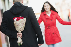 Man holding a flower bouquet behind his back Royalty Free Stock Photos