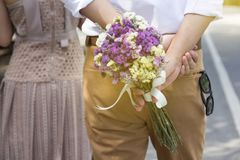 Man holding flowers bouquet walking behind woman. giving flowers stock images