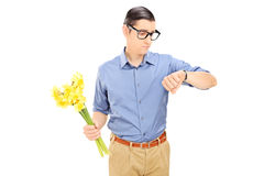 Man holding flowers and checking the time Royalty Free Stock Photos