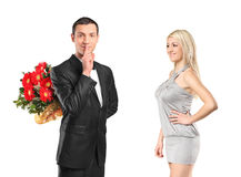 Man holding flowers, gesturing silence Royalty Free Stock Photo