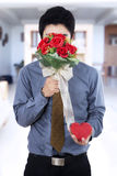 Man holding flowers and gift Royalty Free Stock Photo